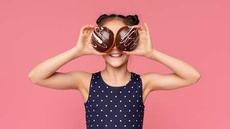 Playful little girl covering her eyes with chocolate donuts, pink panorama background Imagens