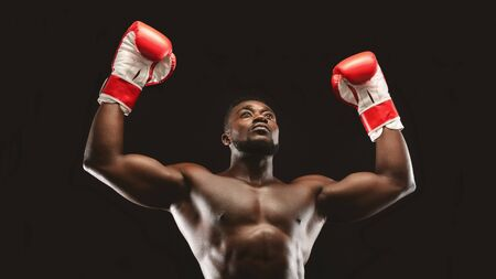Winner. African naked athlete raising hands in boxing gloves, black panorama background Stock Photo