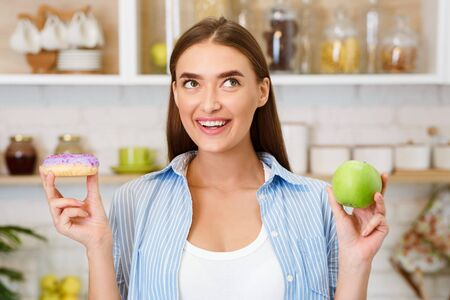 Diet. Beautiful Woman Choosing Between Fruits and Sweets In Kitchen Stock Photo