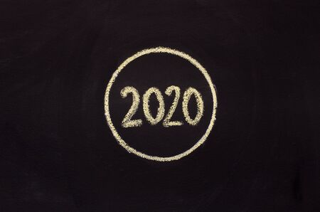 Handwriting with chalk 2020 in round on black background, panorama, copy space