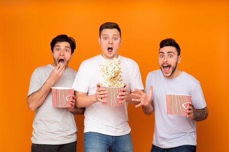 Shocked men eating popcorn and watching scary movie over orange background Reklamní fotografie
