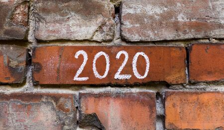 Accidentally finding 2020 text on red bricks wall of old building, panorama, copy space