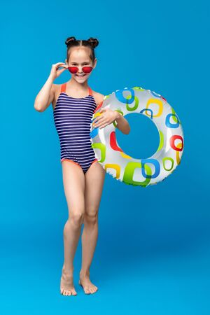 Cute girl ready for swimming, wearing swimsuit and holding inflatable ring, blue studio background