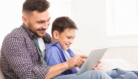 Family time. Young father teaching his son to use special application on digital tablet, panorama with free space Stock fotó