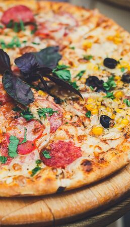 Delicious italian pizza with chicken ham, corns and black olives on thin pastry crust at wooden desk, vertical panorama