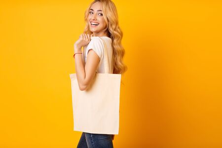 Mockup For Design. Millennial Woman With Cotton Bag Over Yellow Background Фото со стока