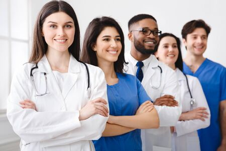 Tem of Confident Doctors And Interns Standing In Hospital With Crossed Arms