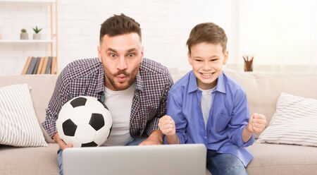 Amazing game. Soccer fans dad and son watching soccer match on laptop online, panorama
