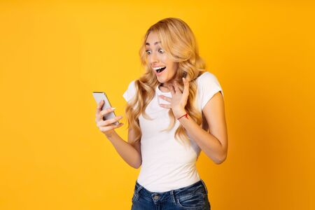 Unexpected Message. Woman Looking At Smartphone Over Yellow Studio Background Archivio Fotografico