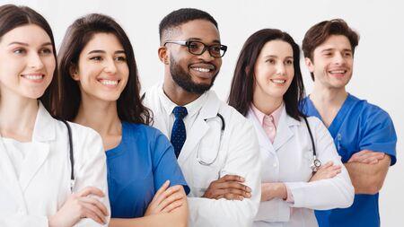 Glückliches medizinisches Personal, das in der Klinik zusammensteht und mit verschränkten Armen posiert