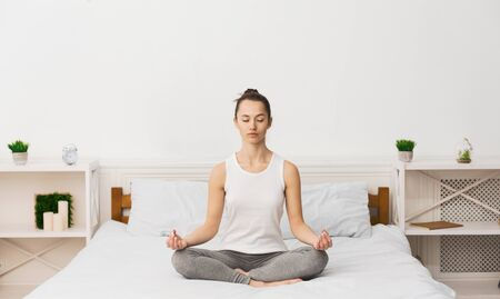 Meditation Concept. Woman Practicing Yoga On Bed, Waking Up In Morning