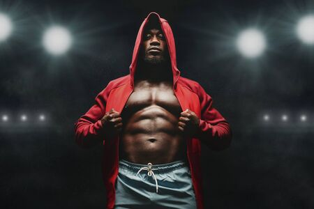 Boxer man workout in boxing ring. African american fighter in hoodie, stadium lights background Imagens