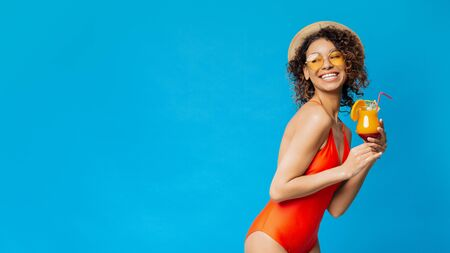 Enjoying summer rest. Cheerful black girl in swimsuit drinking tropical cocktail, blue panorama background with empty space Stock Photo