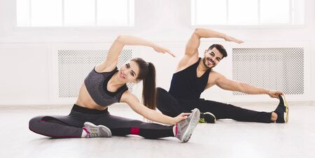 Young fit couple stretching on the floor in light studio, panorama, free space