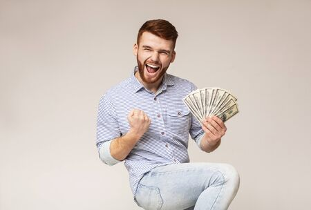 Win a lottery. Young handsome guy happy to have fan of dollars in hand, panorama, free space