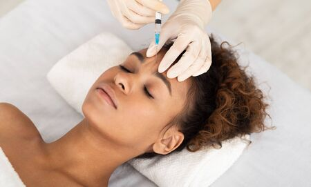 Beauty Procedure. Beautician Expert Injecting Botox In Female Forehead