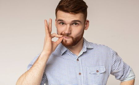 Secret saver. Young guy locking mouth like zip-lock on studio background, panorama, copy space