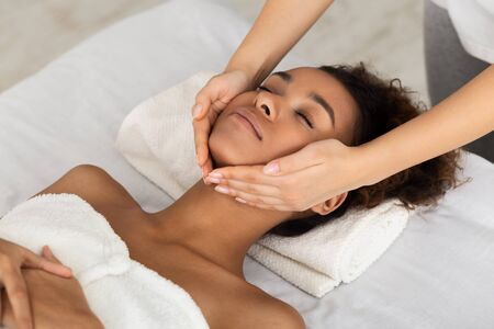 Spa Treatment. African-American Girl Getting Face Massage At Beauty Salon