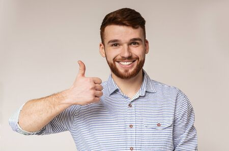 I like it. Young man showing thumb up and smiling on camera against beige background, panorama, copy space