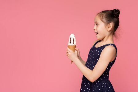 Surprised little girl looking at ice cream cone with amazement, pink panorama background with empty space