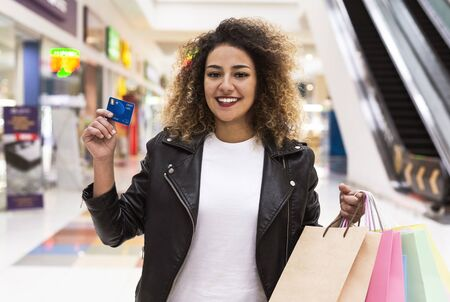 Young african american girl with credit card and shopping bags in mall center, panorama, copy space