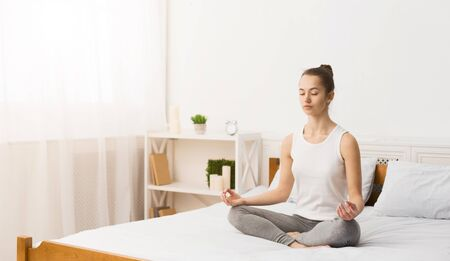Morning Meditation. Woman Practising Yoga In The Morning, Sitting On Bed, Free Space