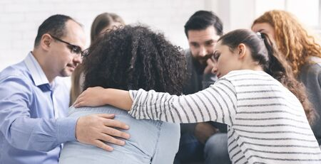Support group meeting. Addicted people comforting upset woman at therapy session, free space Stock Photo