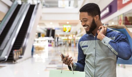 Handsome african american man with shopping bags using cellphone and smiling in mall center, panorama, copy space