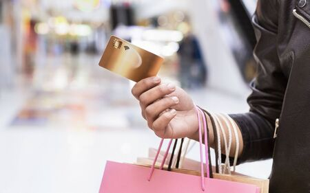 Young african woman holding gold credit card and shopping bags in mall, panorama, copy space