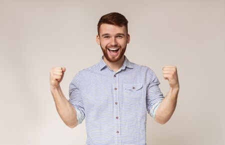 Cheerful guy showing his biceps and smiling on studio background, panorama, copy space