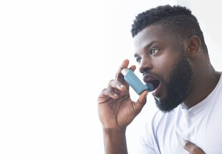 Young african man using asthma inhaler at home. Modern generation sickness, empty space Stock Photo