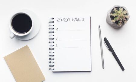 2020 concept. Goals list in notepad with pen and cup of coffee on white office table, panorama, copy space