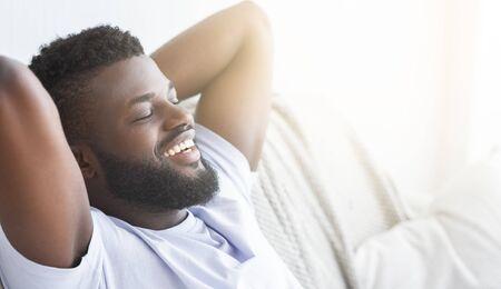 Guten Morgen. Zufriedener schwarzer Kerl, der sich zu Hause entspannt, mit geschlossenen Augen liegt, Panorama mit Sonneneruption, freier Raum