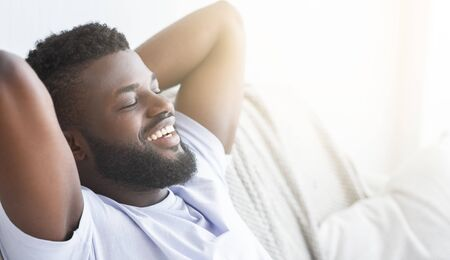 Happy morning. Satisfied black guy relaxing at home, lying with closed eyes, panorama with sun flare, free space