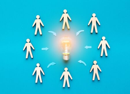 Crowdfunding concept. Wooden cut out human figures around light bulb on blue background.
