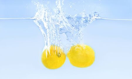 Pair of lemons sinking into water with air bubbles, blue background