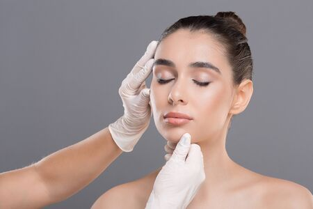 Plastic surgery concept. Young woman on consultation at beautician, grey background