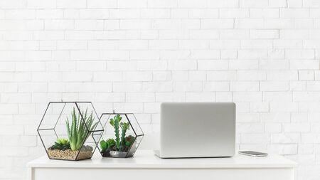 Escritorio blanco con computadora portátil y plantas de interior en el fondo de la pared de ladrillo blanco, espacio de copia Foto de archivo