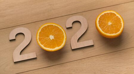 Creative 2020 concept. Wooden numbers with oranges instead of zero on wooden background, panorama, copy space Stock Photo
