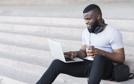 Happy african guy having rest in the city and using Internet on laptop, panorama, copy space