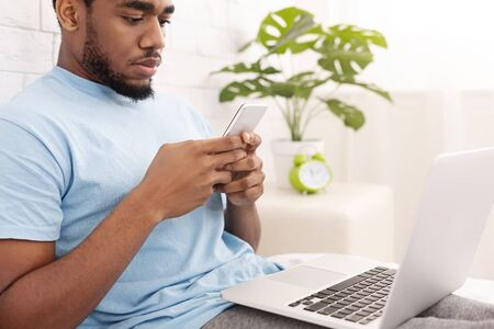 Two factor authentication. Black man using phone and laptop in bed, reading security code to access financial data online, empty space