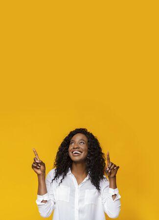 Grande offerta! Eccitata donna afroamericana che punta verso l'alto nello spazio vuoto, sfondo giallo Archivio Fotografico