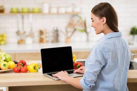 Blog culinario. Donna che cerca ricette online su laptop con schermo vuoto