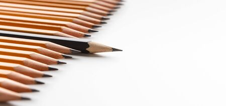 Uniqueness concept. Black pencil sticking out of row with similar ones, white panorama background with free space
