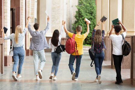 Students walking in college campus after passing test, back view Stock Photo