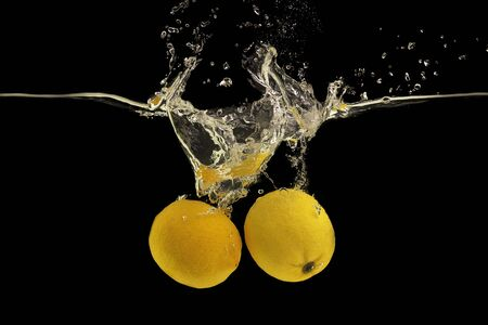 Yellow fresh lemons under clear water with splash and drops, black background Banco de Imagens