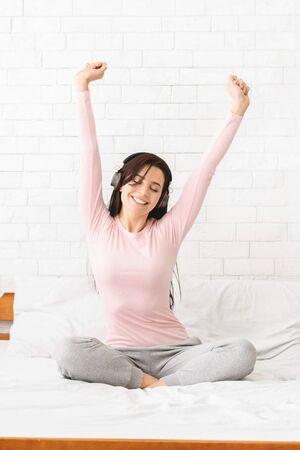 Gelukkige vrouw in koptelefoon luisteren naar muziek van smartphone, dansen in bed thuis, kopieer ruimte