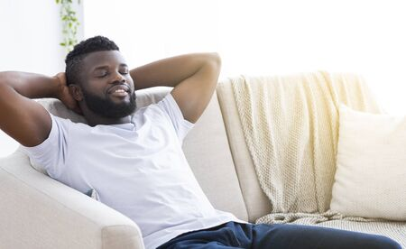 Pleased african-american man relaxing at home, sitting on couch with closed eyes, copy space Reklamní fotografie