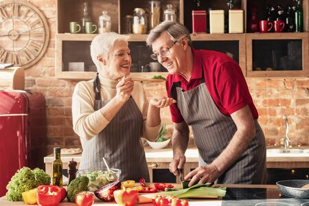 Happy senior couple in aprons tasting food and smiling, cooking healthy lunch together in kitchen 스톡 콘텐츠