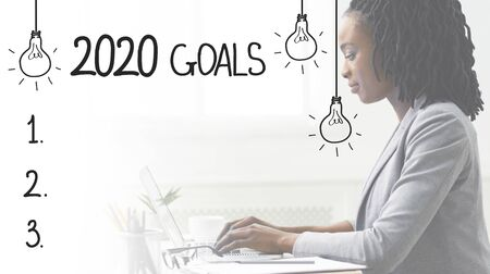 2020 goals concept. African business woman typing on laptop near blank checklist, free space Stock Photo
